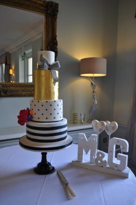Modern black and white cake with gold leaf.