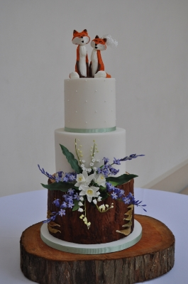 Delightful rustic 3 tier wedding cake with handmade sugar flowers and handmade foxes.